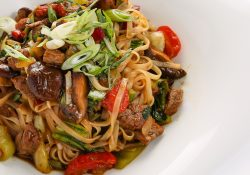 Drunken noodles with chive garnish